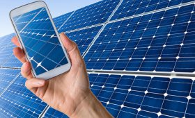 Closeup of mobile phone taking picture of blue solar panels